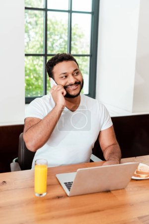 Photo pour Happy african american freelancer talking on smartphone near laptop and breakfast on table - image libre de droit