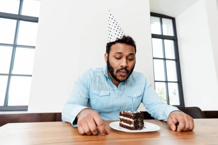 Photo for African american man in party cap celebrating birthday alone and blowing out candle on birthday cake - Royalty Free Image