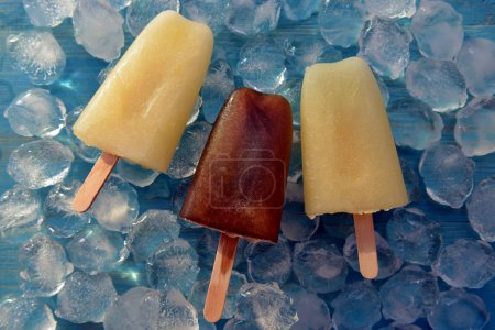 Fruit sorbet on a stick against a background of ice cubes. Frozen cola on a stick. Ice cream from melon and cola. Ice cubes on a blue wooden background.
