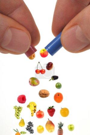 Photo pour Compléments alimentaires concept avec capsules de fruits sur fond blanc - image libre de droit