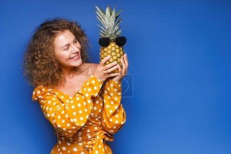 Photo pour Femme et ananas sur la tête, debout sur fond de couleur - image libre de droit