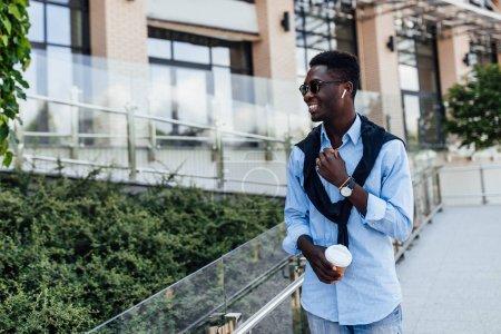 Photo pour Joyeux jeune homme souriant dans la rue, sélectivité - image libre de droit