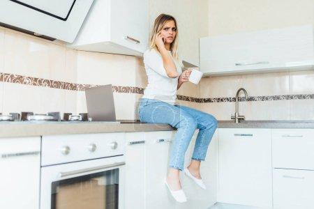 Photo pour Jeune femme assise sur une table de cuisine et parlant au téléphone - image libre de droit