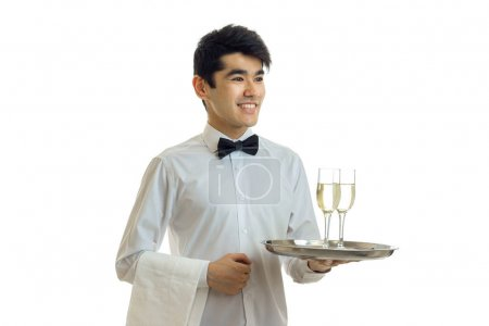 smiling handsome waiter with black hair and shirt holding a tray with two glasses of wine