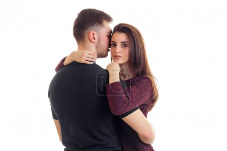 attractive girl looks straight and hugs a young guy in the black shirt