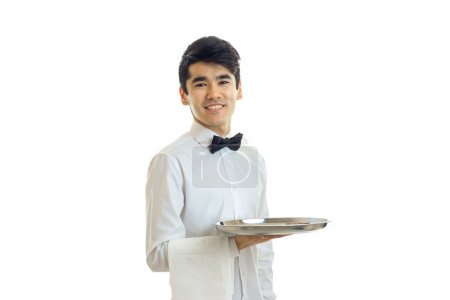 attractive smiling young waiter looks at the camera and holding a tray with a towel