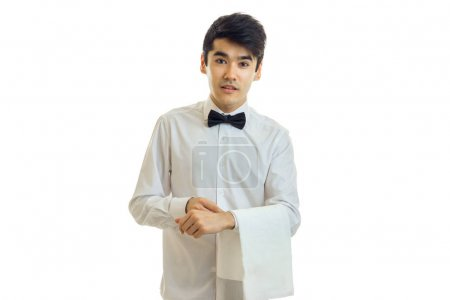 charming young waiter stands upright with cloth on hand