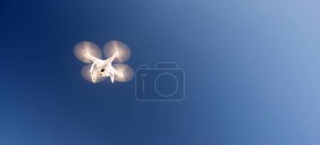 Photo pour Un Quadcopter en vol stationnaire avec un ciel bleu foncé dans un long panoramique composition - image libre de droit