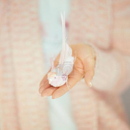 Photo pour Les mains de la femme tenant petit oiseau artificiel dans ses mains, les couleurs pastel rose clair peuvent être utilisées comme fond romantique - image libre de droit