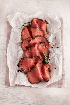 Photo for Sliced medium rare grilled roast beef ribeye steak on white wooden kitchen plate - Royalty Free Image