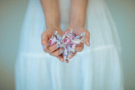 Photo pour Mains de femme tenant des bonbons vintage, sensuelle prise de vue en studio rural peut être utilisé comme fond - image libre de droit