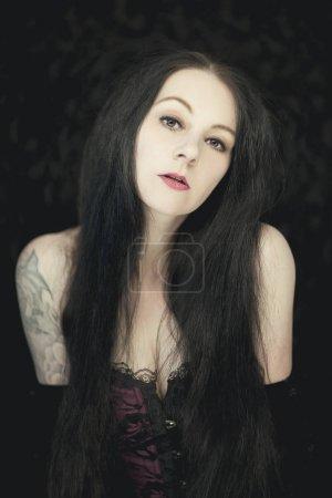 Photo pour Belle femme de style gothique allemand avec de longs cheveux noirs brillants regardant dans la caméra - image libre de droit