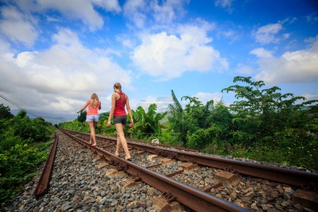 backside view European two young girls in shorts walk along railway past plants against blue sky