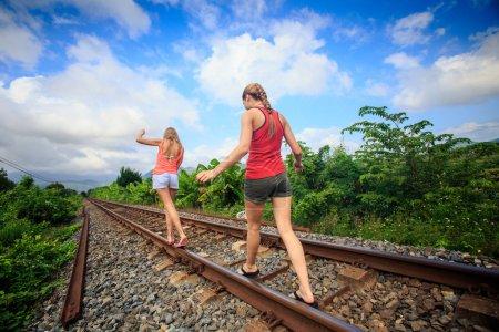 Photo pour Vue de dos deux jeunes filles blondes en gilets shorts marchent le long de la voie ferrée par des plantes vertes contre des nuages de ciel bleu - image libre de droit