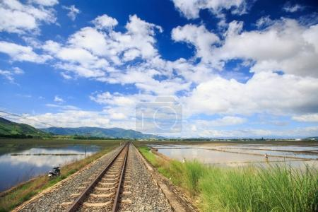 railway track among water rice fields vanishes into space against hills on horizon blue sky clouds