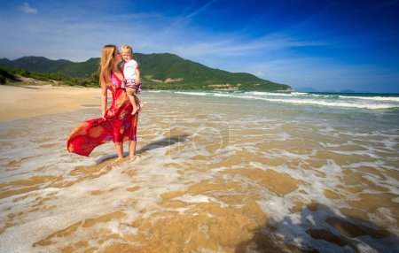 young blond woman in long red dress in foamy wave surf holds clasps daughter to breast against green hill