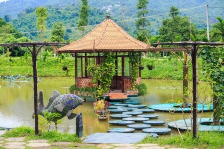 pavilion in middle of pond with wooden path