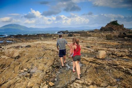 backside view distant guy blonde girls in vest shorts walk along rocky coast against azure sea blue cloudy sky