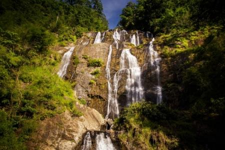 pictorial high waterfall on steep rocks between tropical jungle under sunlight in Vietnamese highland