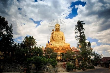beautiful large golden Buddha statue sending blessing to everybody against blue sky with white clouds