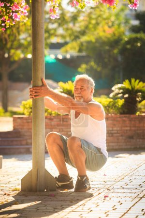 Man Does Morning Exercises Squats by Pole
