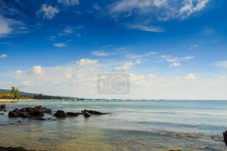 different rocks in transparent shallow water near coast against green shore distant boats and cloudy blue sky