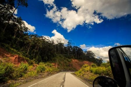 Asphalt Road along Wooded Hill out of Bus Window Blue Sky