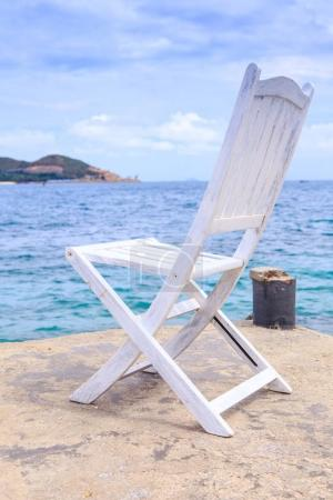 White Wooden Chair on Stone Pier