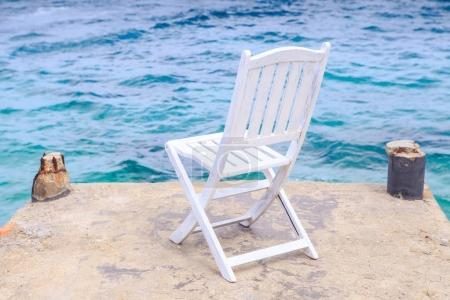 White Wooden Chair on Stone Pier against Azure Sea