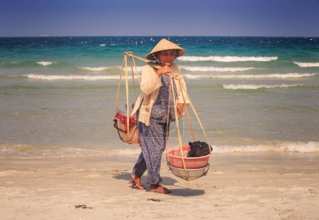 NHA TRANG/VIETNAM - APRIL 16 2017: Closeup old woman vendor in Vietnamese hat with baskets on yoke stands by ocean surf on sand beach against azure sea on April 16 in Nha Trang