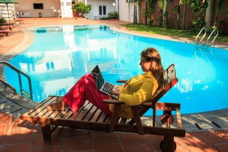 blond girl in clothes lies on chaise-longue in shade with laptop at swimming pool in resort city