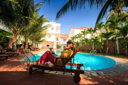 blond long haired dressed girl sits in folding chair in palms shadow with notebook at hotel swimming pool