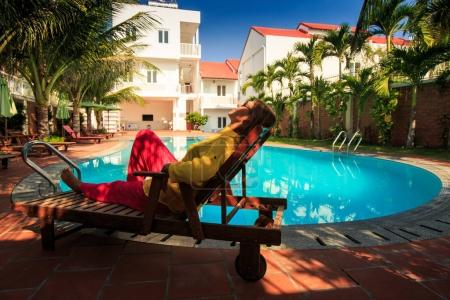 girl in clothes rests on chaise-longue in shade at hotel swimming pool surrounded by palms in resort city