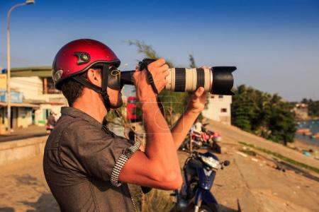 closeup European professional photographer in red helmet photos with large camera sea from sea-front