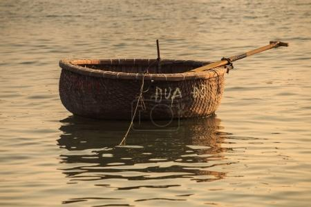 Photo for Closeup brown Vietnamese round wicker basket fishing boat with paddle on sea water at sunset - Royalty Free Image