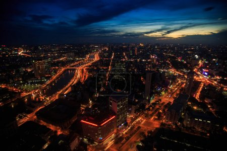 pictorial panorama of large night city with brightly lit river embankments under dramatic dark blue sky in Saigon