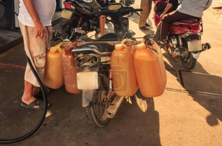 closeup man fills petrol to orange tanks fixed at scooter rear wheel against other scooters in Vietnam