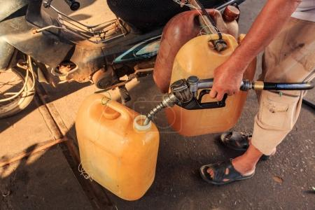closeup man hand holds filling device refuels petrol into orange tanks fixed on motorbike at street station in Vietnam