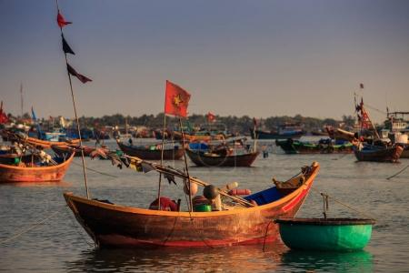 closeup colourful Vietnamese long and round fishing boats in azure ocean bay against coast village at sunset