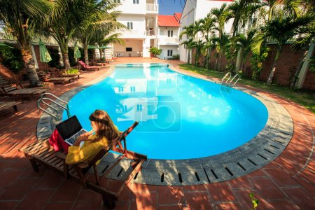 blonde girl dressed in long sleeves blouse sits in folding chair under palms with notebook at hotel pool