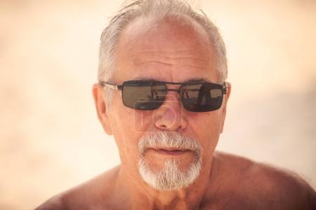 portrait of grey haired bearded old man in modern black sunglasses against light background