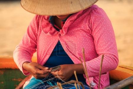 closeup local woman in national straw hat hiding face and pink blouse mends fishing net against sand beach in Vietnam