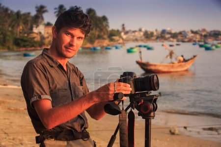 closeup young guy professional photographer adjusts equipment looks at camera smiles on sand beach