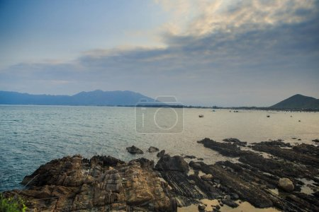 speckled with water brown beach stones against calm ocean distant hills boats and blue sky with clouds