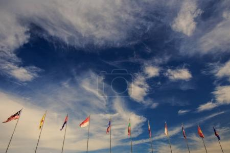 row of colourful banners on flagstaffs against bright blue sky with beautiful white clouds in Vietnam