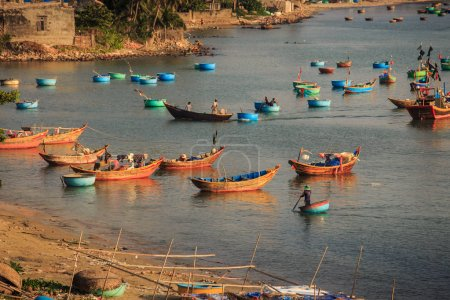 colourful long and round fishing boats in tranquil azure ocean near coast with village at sunset in Vietnam