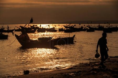 Vietnamese traditional fishing boats in sea against bright sunset light reflection and man silhouette on foreground