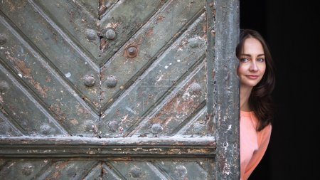 Young cute girl peeks out from behind vintage door...