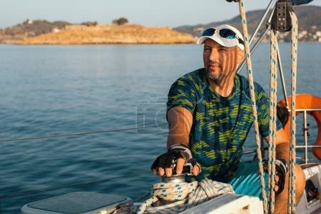 handsome man on sailing boat.