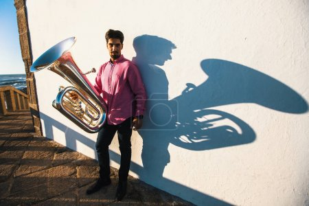 Musician with tuba near the  wall